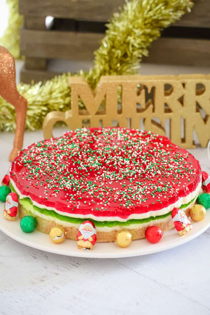 A round Jelly Cake made with green, white and red layers, and sprinkles on top, surrounded with Christmas decorations and chocolates