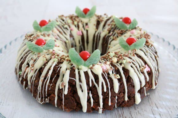 A cake decorated like a Christmas wreath, drizzled with white chocolate, and topped with lollies to resemble holly