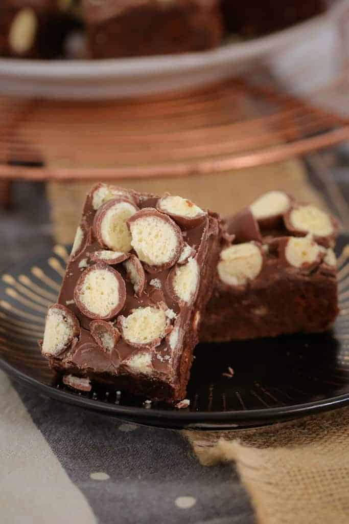 Pieces of chocolate slice, topped with chopped Maltesers and served on a black plate