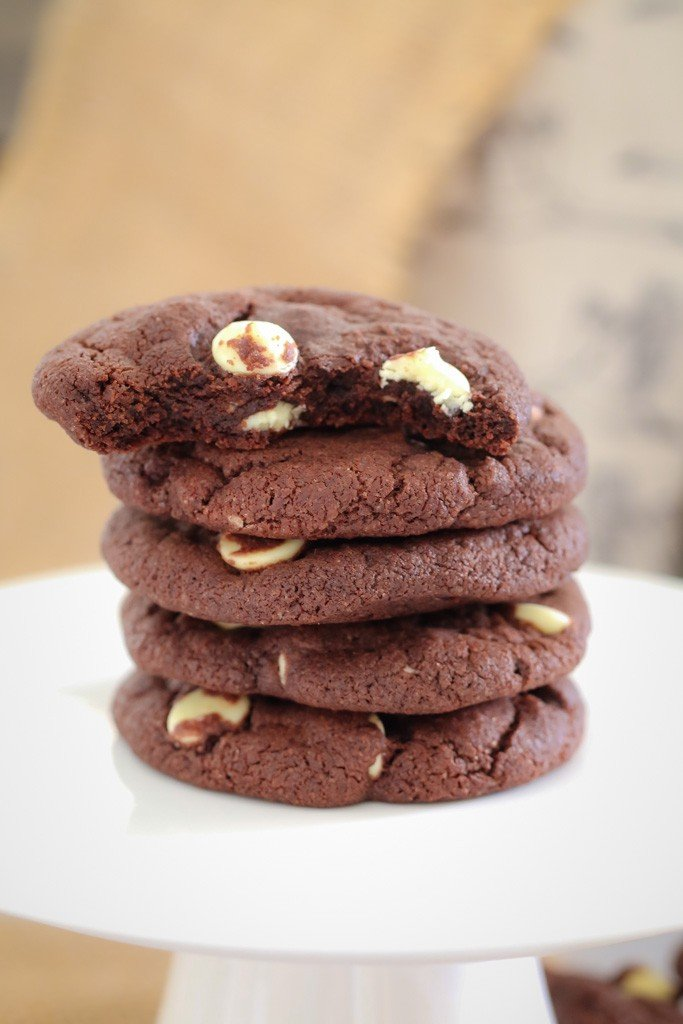 A stack of chocolate cookies with white chocolate bits and a half-eaten cookie on top.