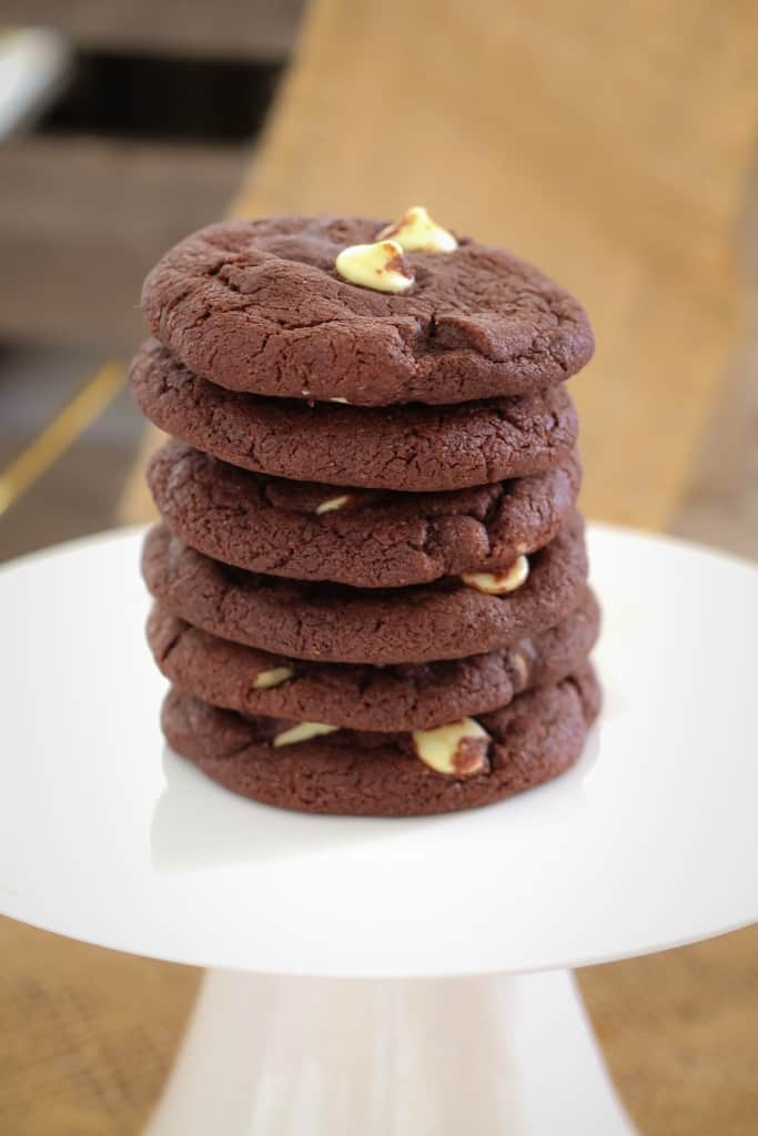 A stack of 6 double cookies on a white cake stand.