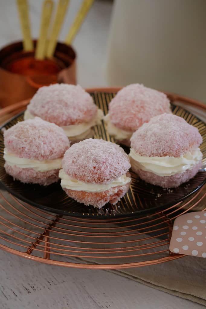 A plate of five pink, coconut covered jelly cakes filled with cream