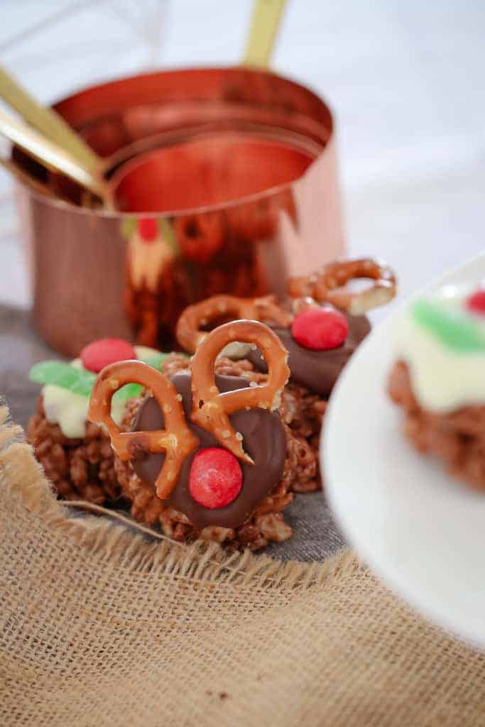 Chocolate Christmas Crackles decorated as reindeer and as Christmas puddings in front of a set of copper measuring cups