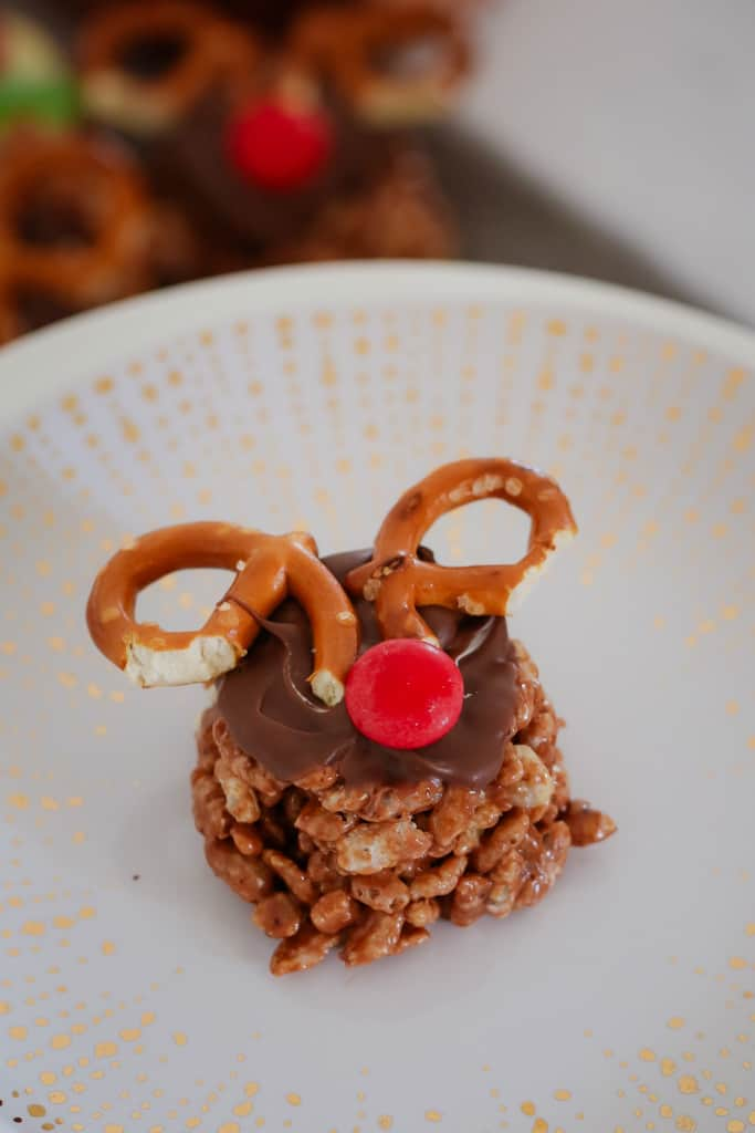 A chocolate Christmas Crackle on a plate, decorated with chocolate, pretzels for antlers and a red M&M as a nose