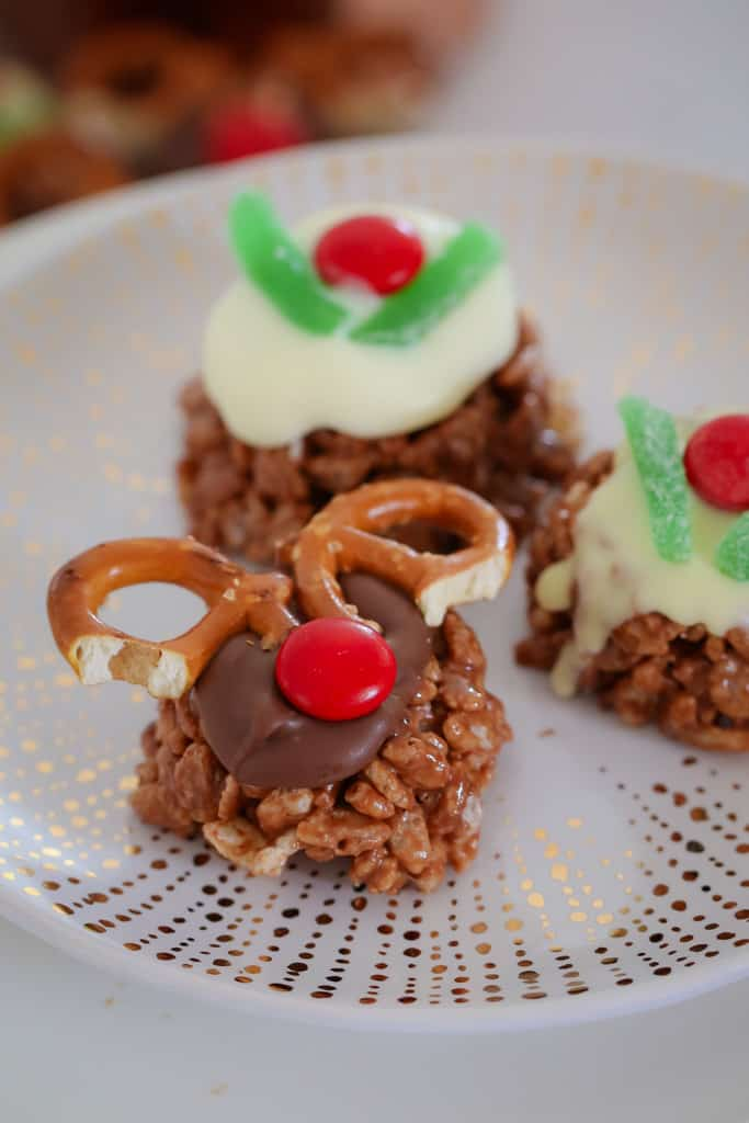 A white and gold plate with chocolate Christmas Crackles decorated as reindeer and Christmas puddings