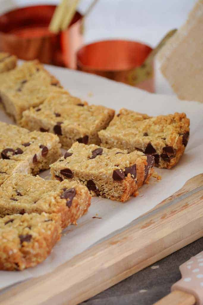 A slice made with oats and chocolate chips cut into pieces and sitting on baking paper