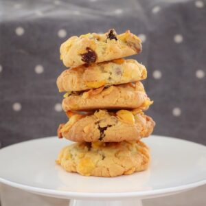 A stack of chocolate chip and sultana cookies on a round cake tray