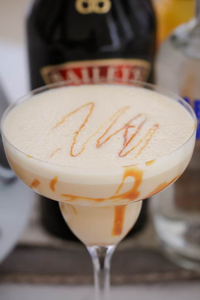 A cocktail glass filled with a cream cocktail with caramel swirls in front of a bottle of Baileys