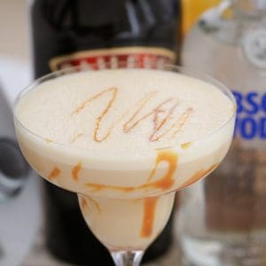 A close up of a creamy cocktail with caramel swirls in a cocktail glass
