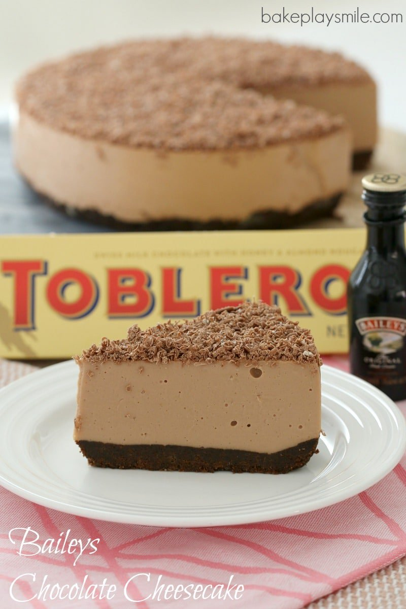A slice of chocolate cheesecake on a plate, with a bar of Toblerone and more cheesecake behind