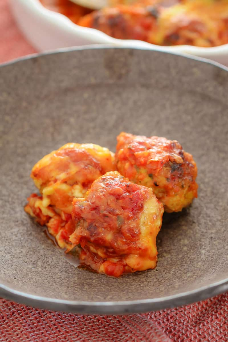 Tomato and chicken meatballs on a plate.