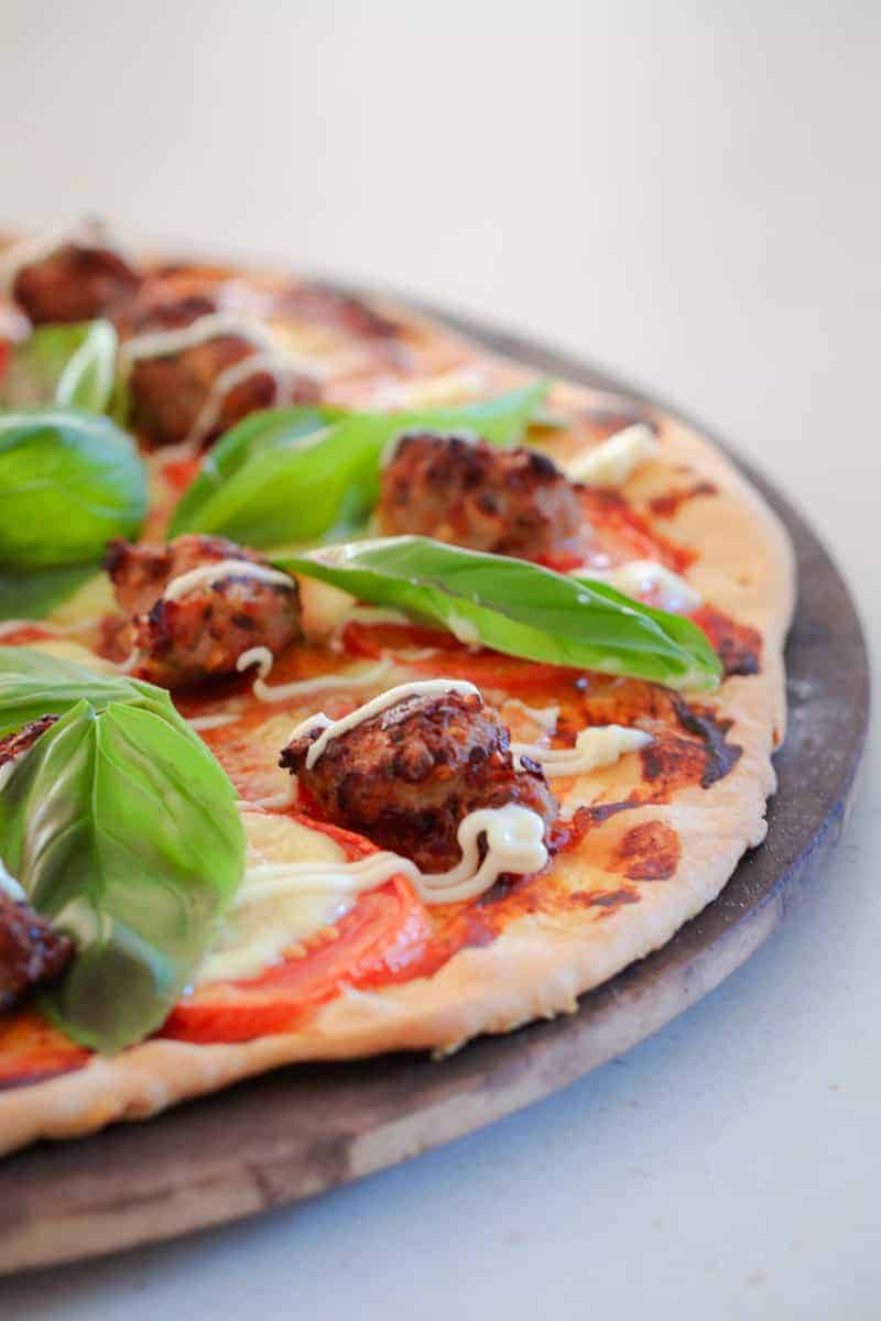 A slice of pizza topped with tomato, pork sausage, bocconcini and fresh basil leaves on a pizza board