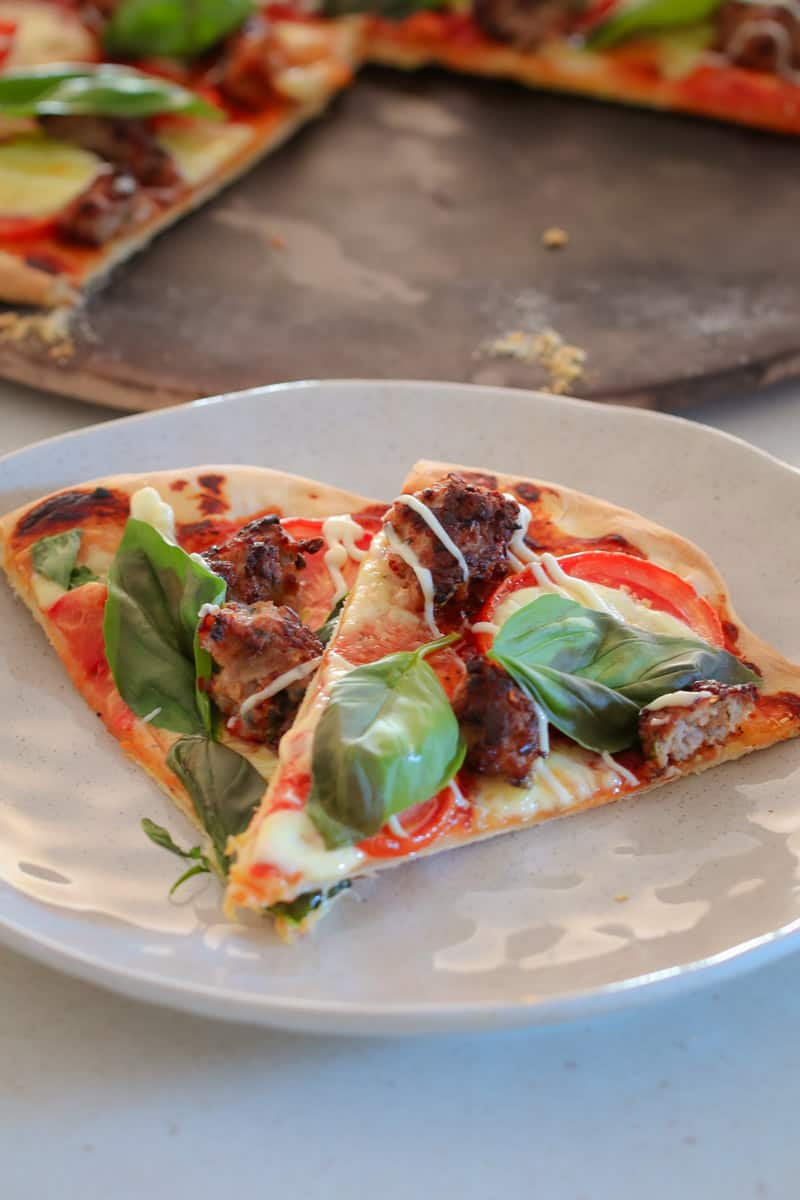 Slices of pizza topped with tomato, pork sausage, bocconcini and fresh basil leaves on a white plate