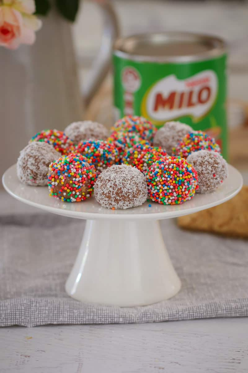 A white cake stand with round balls, some decorated with coconut and some with sprinkles, in front of a tin of Milo