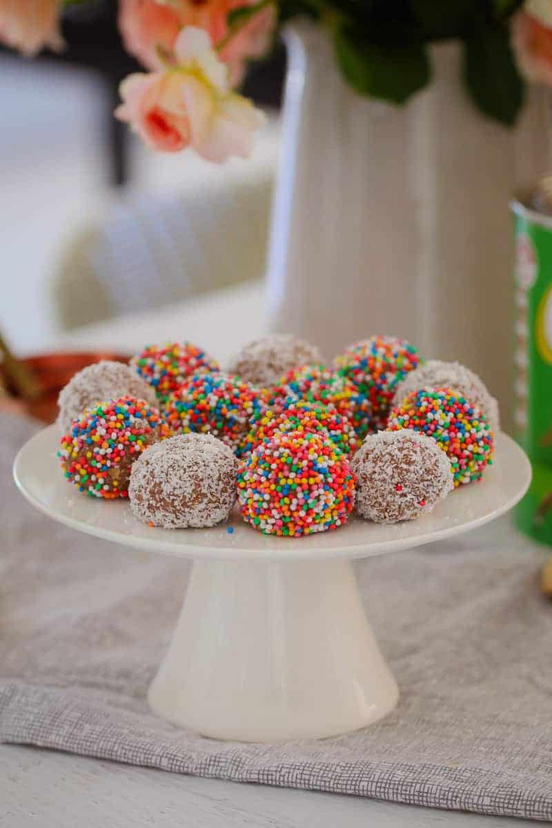 A white cake stand of round balls, some rolled in coconut and some in coloured sprinkles