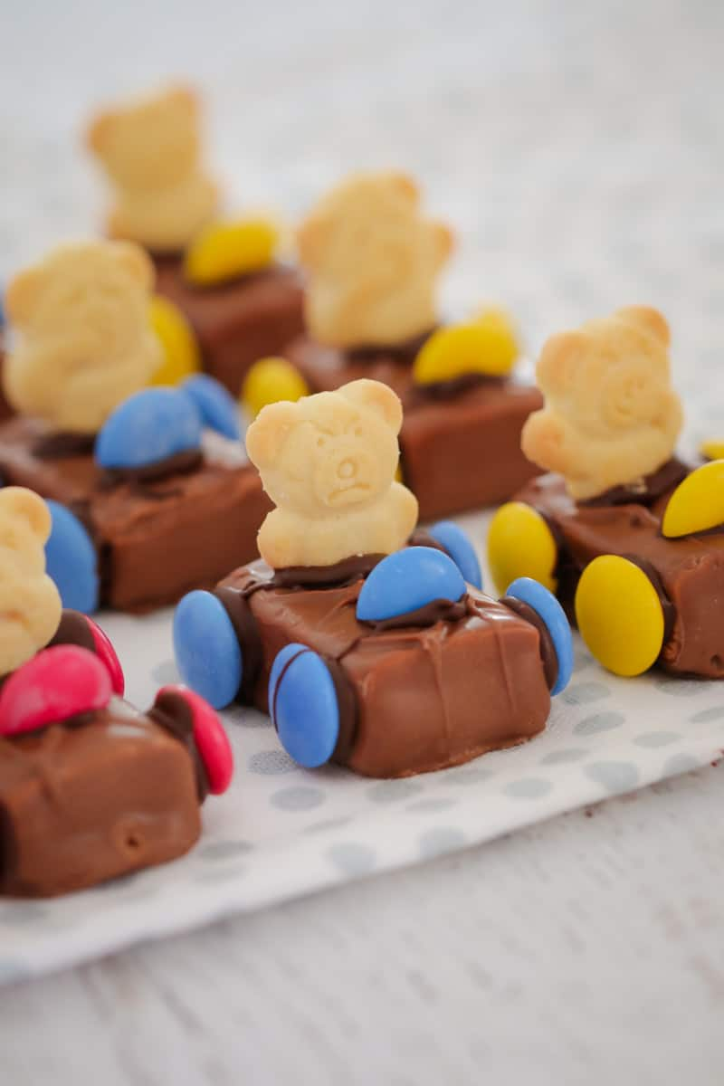 A close up of Tiny Teddy Racing Cars made with a Milky Way, Smarties for wheels and a Tiny Teddy biscuit as the driver