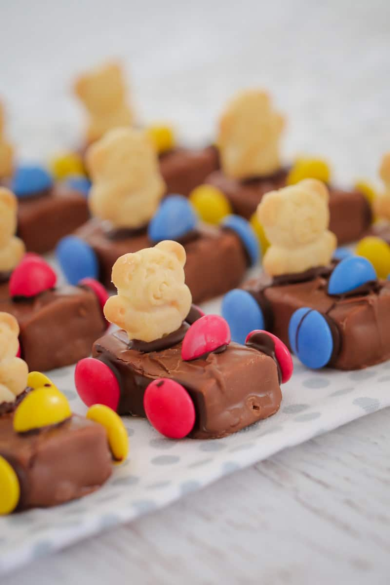 A close up of Tiny Teddy Racing Cars made with a Milky Way, coloured Smarties for wheels and a Tiny Teddy biscuit as the driver