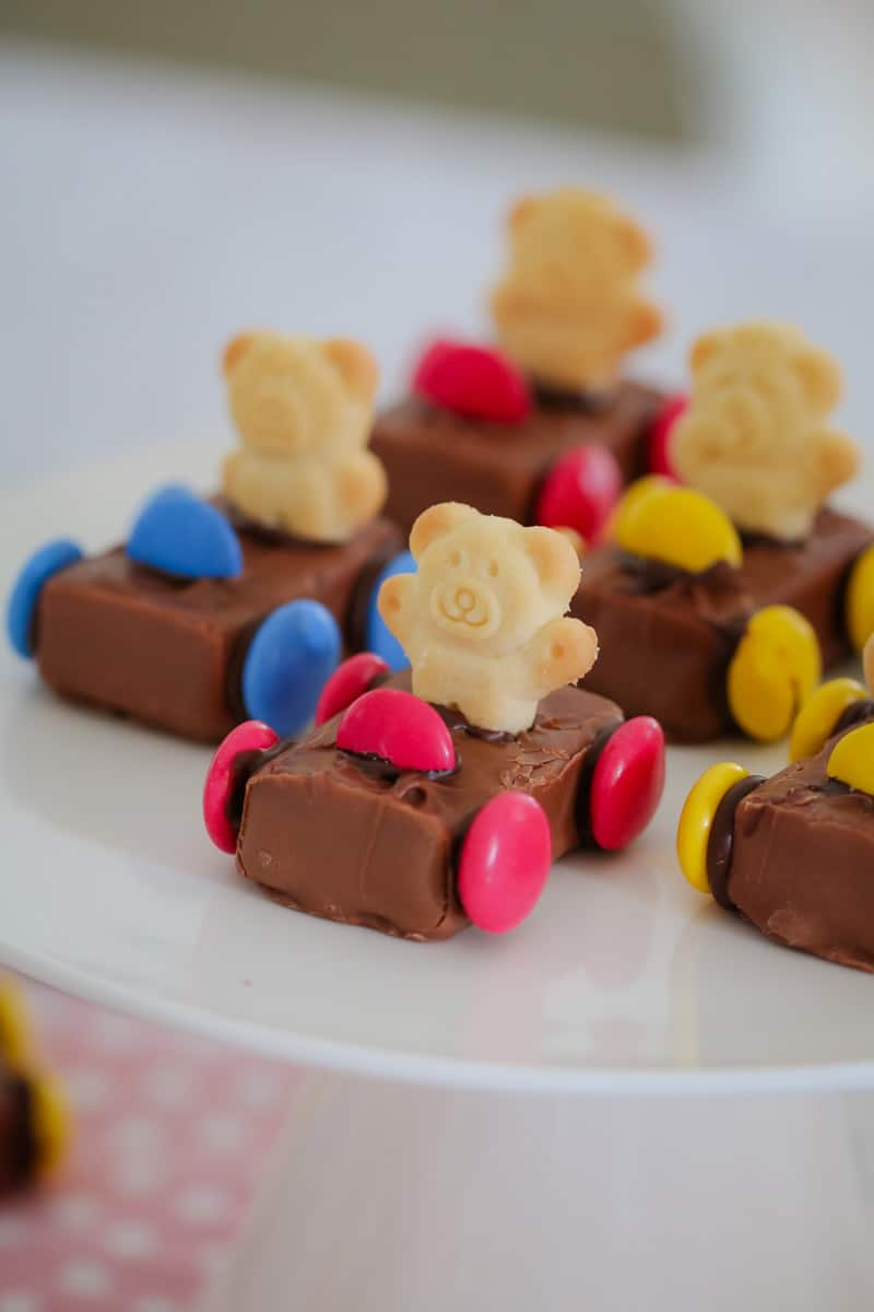 A plate of Tiny Teddy Racing Cars made with a Milky Way, coloured Smarties for wheels and a Tiny Teddy biscuit as the driver