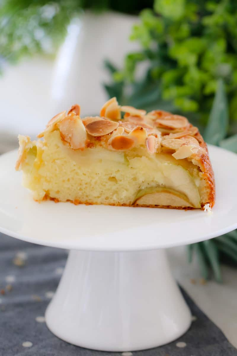 A slice of vanilla butter cake with layers of apple and almonds.