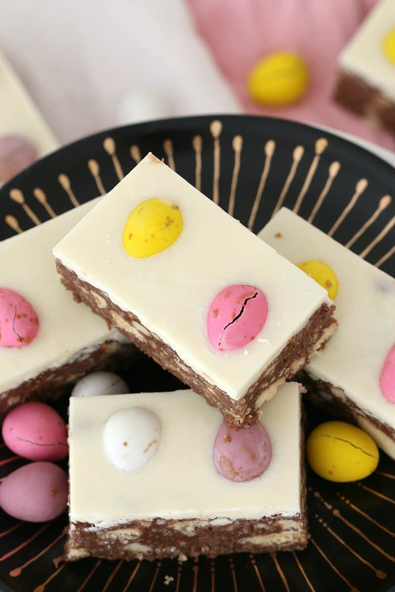 Pieces of a no-bake chocolate slice topped with white chocolate and decorated with coloured mini Easter eggs served on a black and gold plate