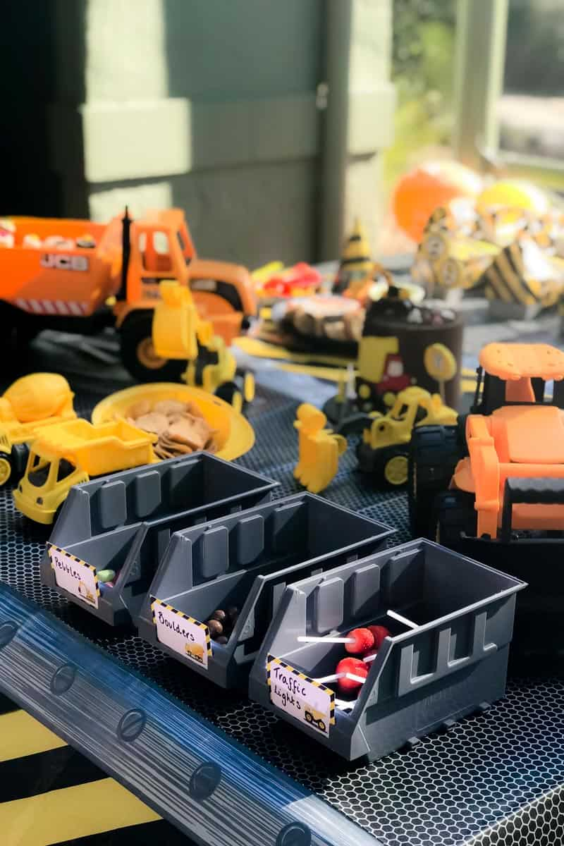 Mini toy trucks, graders and trays in front of Digger party food