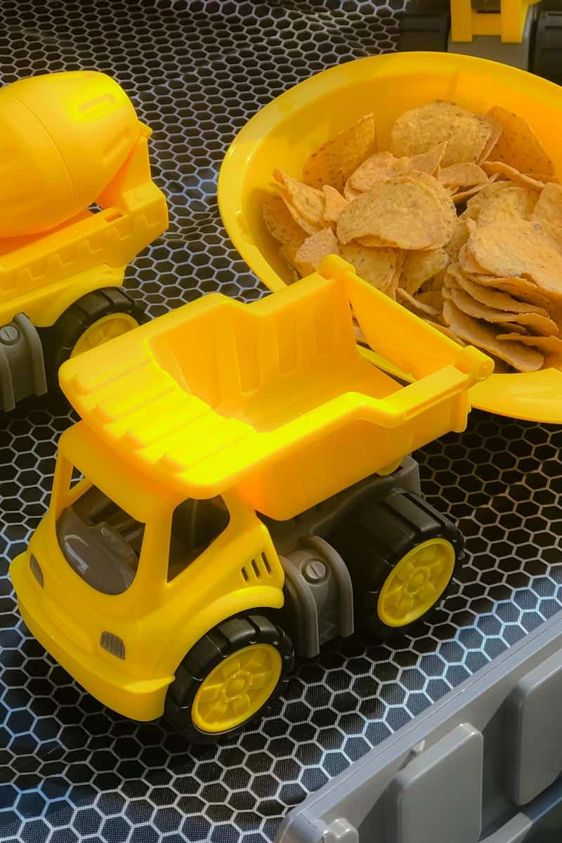 A yellow mini tip-truck in front of a bowl of crisps
