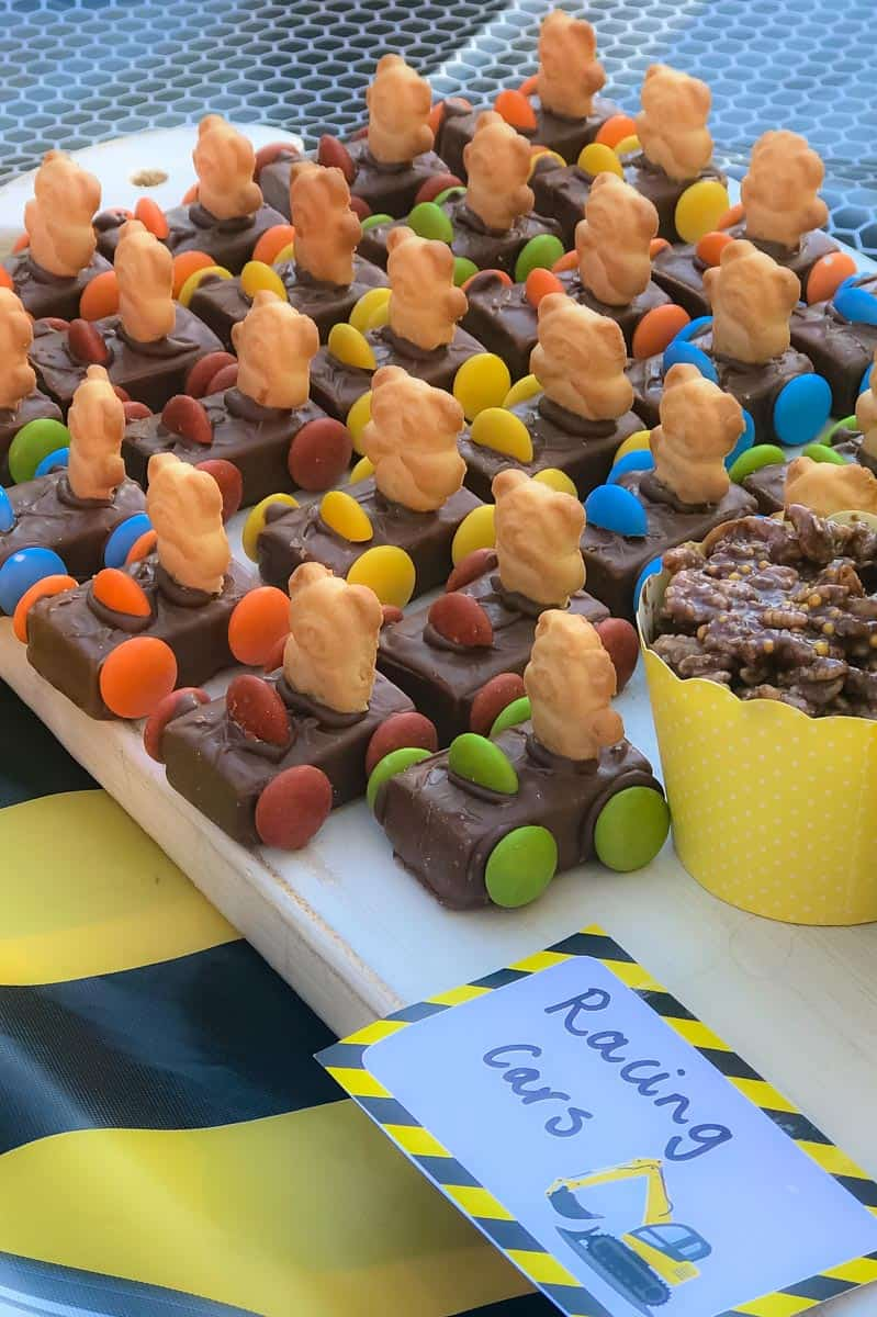 A group of mini chocolate bars decorated with smarties and tiny teddy biscuits to resemble Teddy Cars