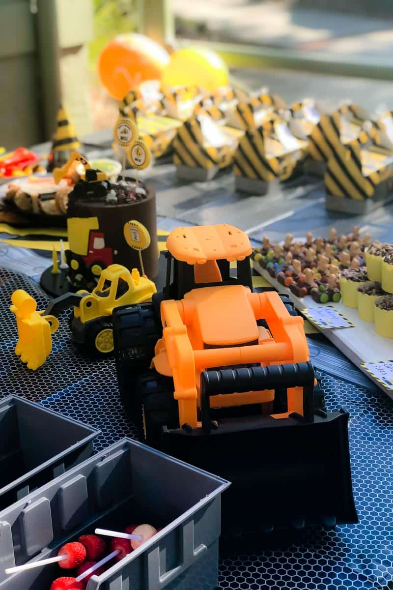 Toy diggers and graders inn front of kids party food