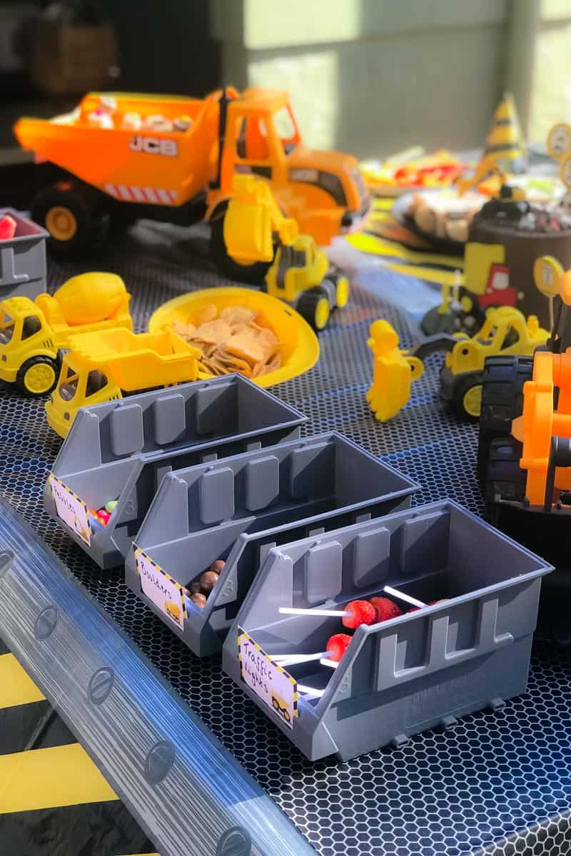 A close up of a toy trucks and trays filled with lollies for a Digger Party