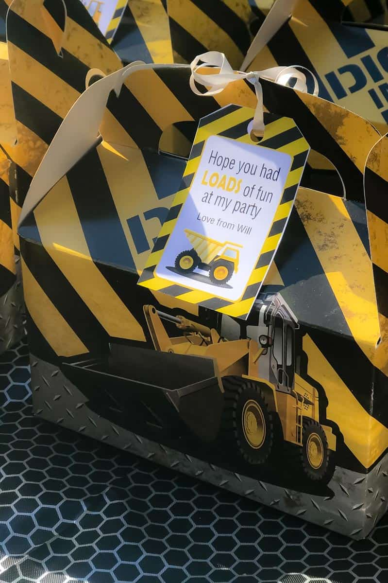 A close up of a yellow and black stripped party box with a picture of a truck on the side and a label attached
