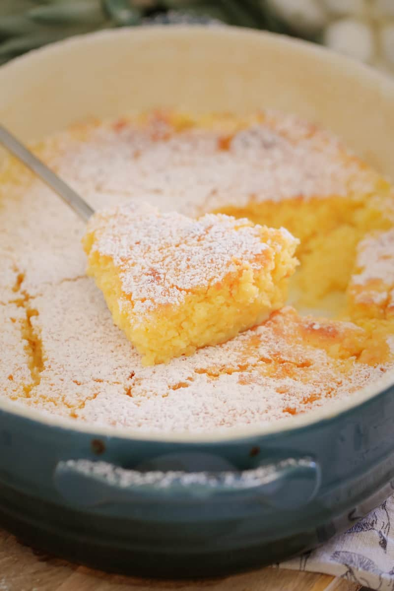 Lemon pudding being served from a baking dish.