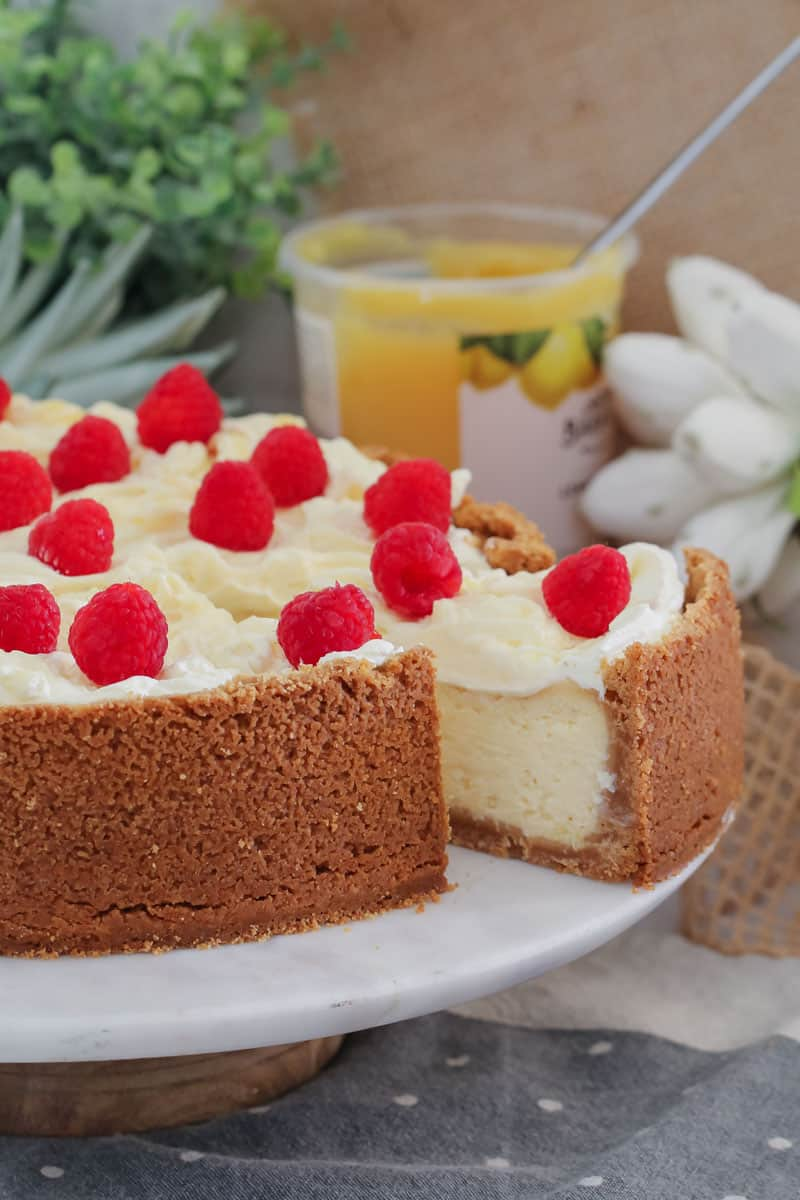 A cheesecake topped with whipped cream and fresh raspberries with one slice partly removed