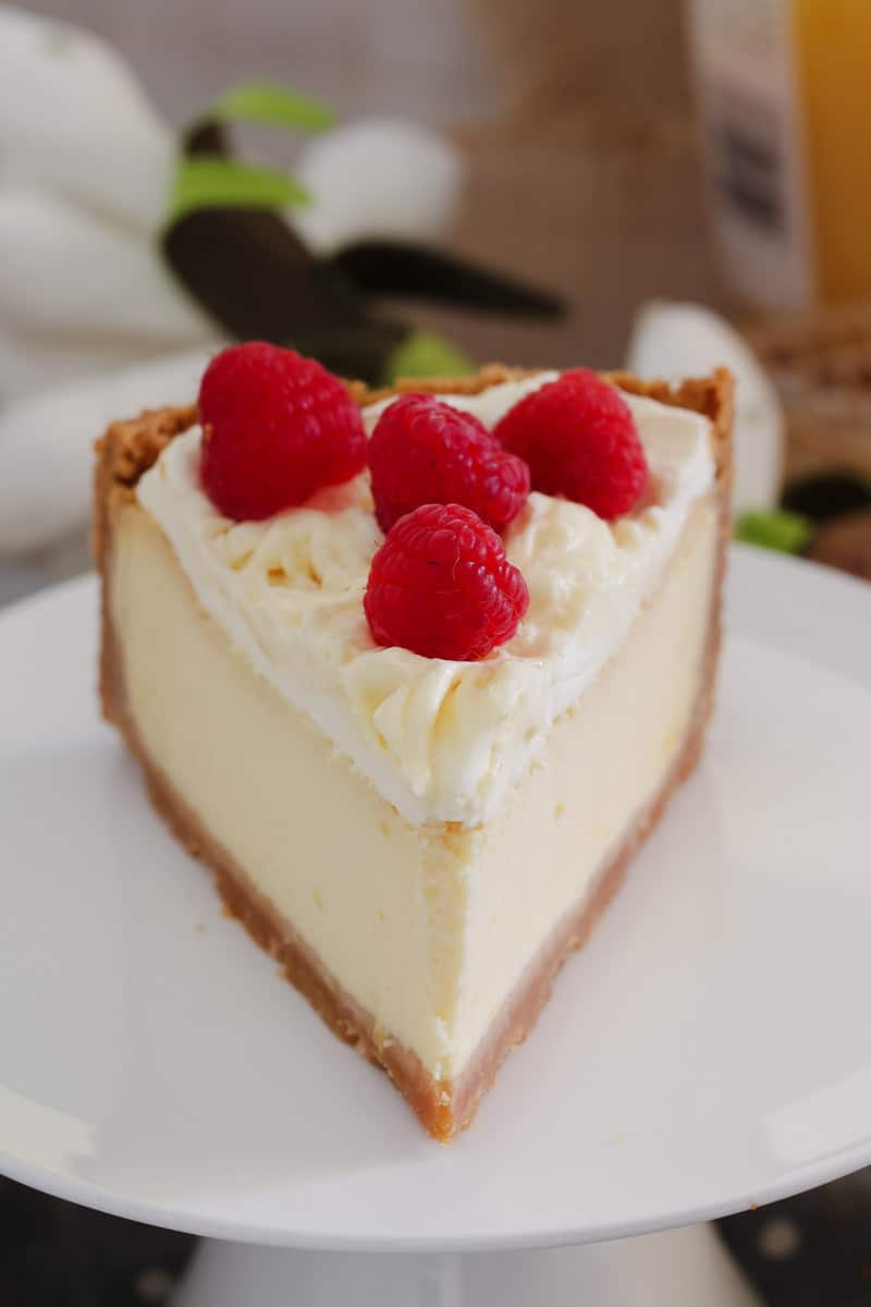 A serve of cheesecake topped with whipped cream and fresh raspberries showing smooth lemon cheesecake filling
