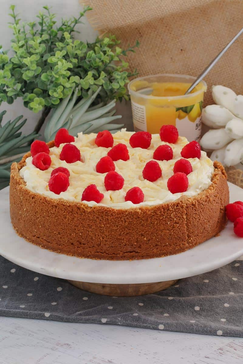 The ultimate classic Baked Lemon Cheesecake... a delicious biscuit base filled with creamy, tangy lemon cheesecake and topped with whipped cream, swirls of lemon curd and fresh raspberries.