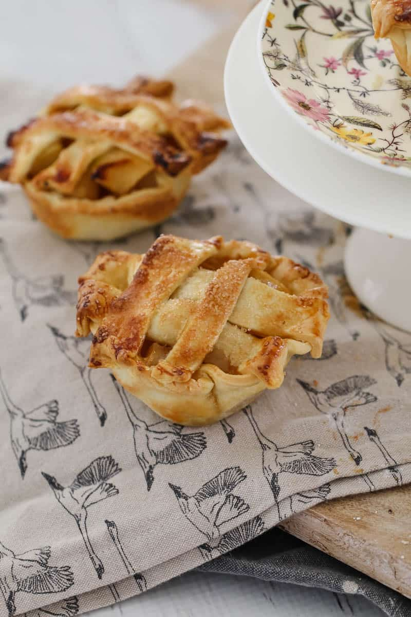 Two mini apple and caramel pies topped with pastry lattice sitting on a tea towel