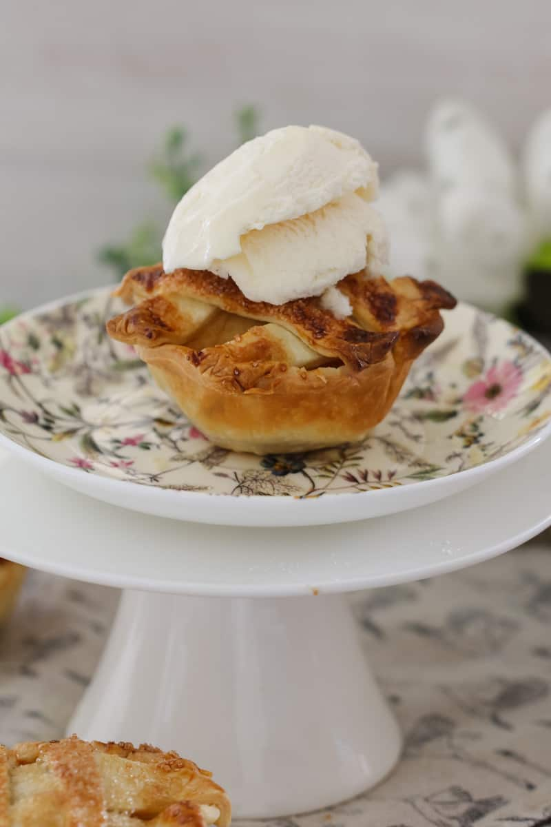 A mini apple and caramel pie with a dollop of ice cream on top, sitting on a floral plate