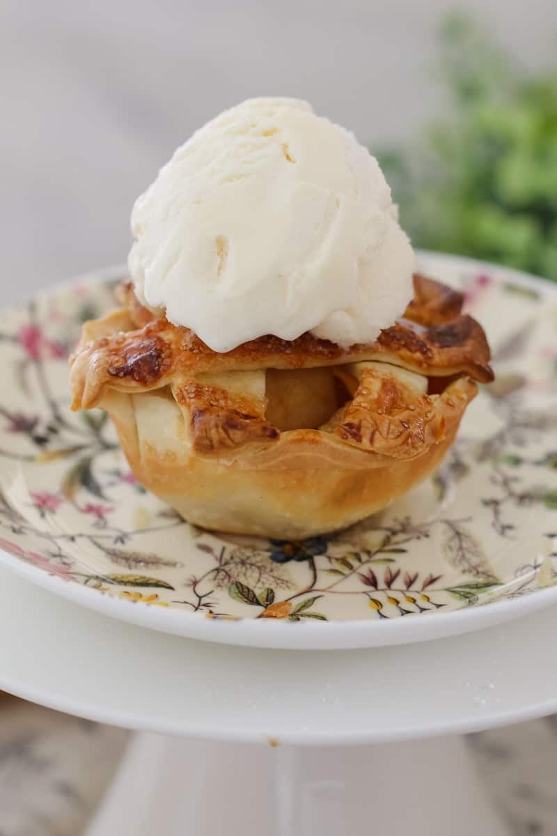 A mini apple and caramel pie served with a dollop of ice cream on a floral plate