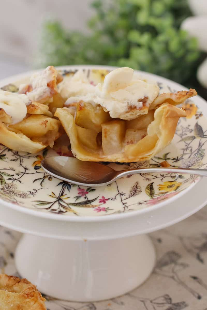 A close up of a cut apple and caramel mini pie served on a floral plate with a spoon