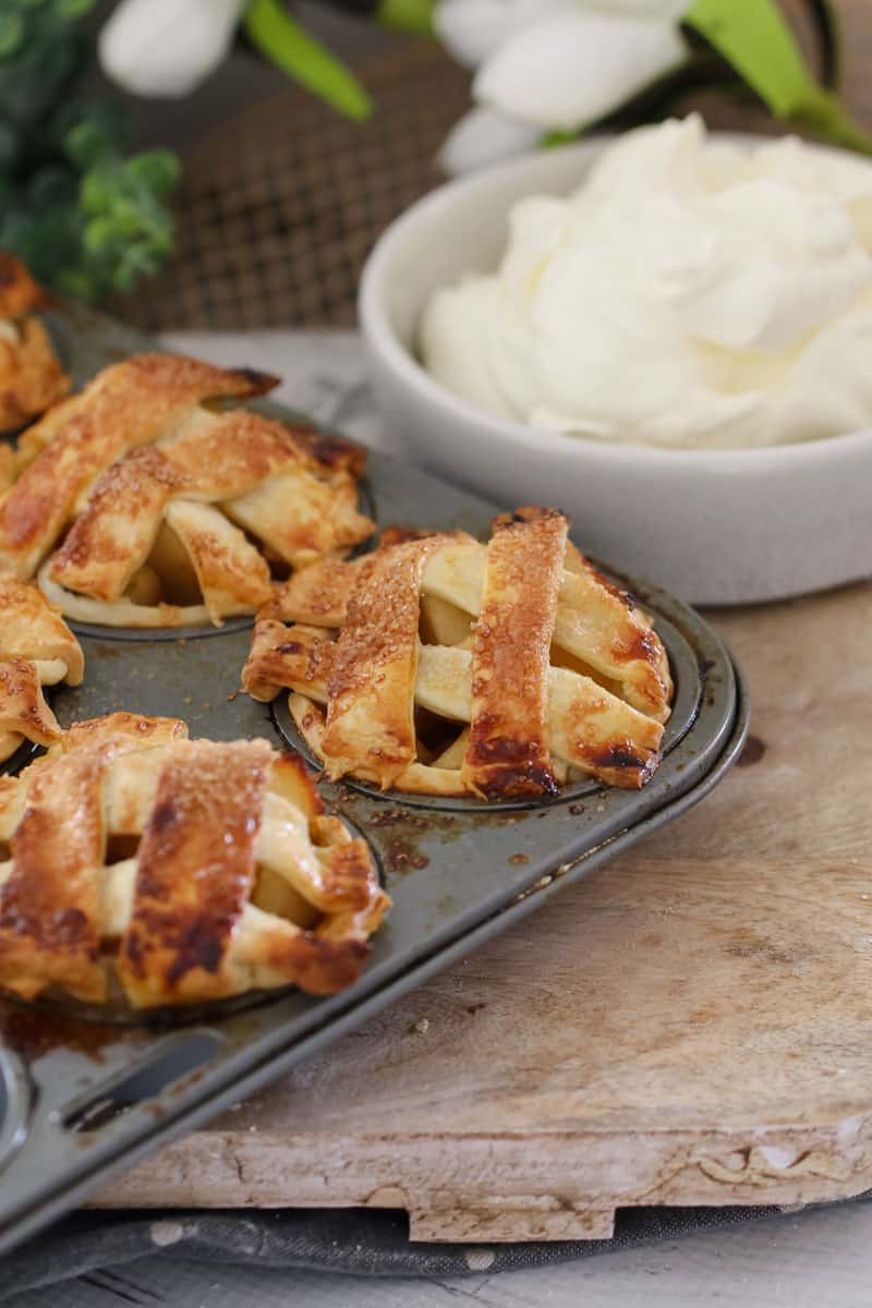 A muffin baking tray of mini apple and caramel pies topped with pastry lattice in front of a bowl of whipped cream