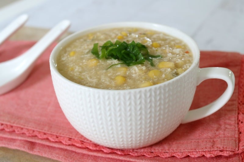 A cup of chicken and corn soup with spring onions on top.