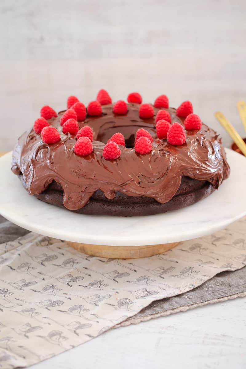 A bundt shaped chocolate mud cake on a serving plate, decorated with chocolate ganache and fresh raspberries