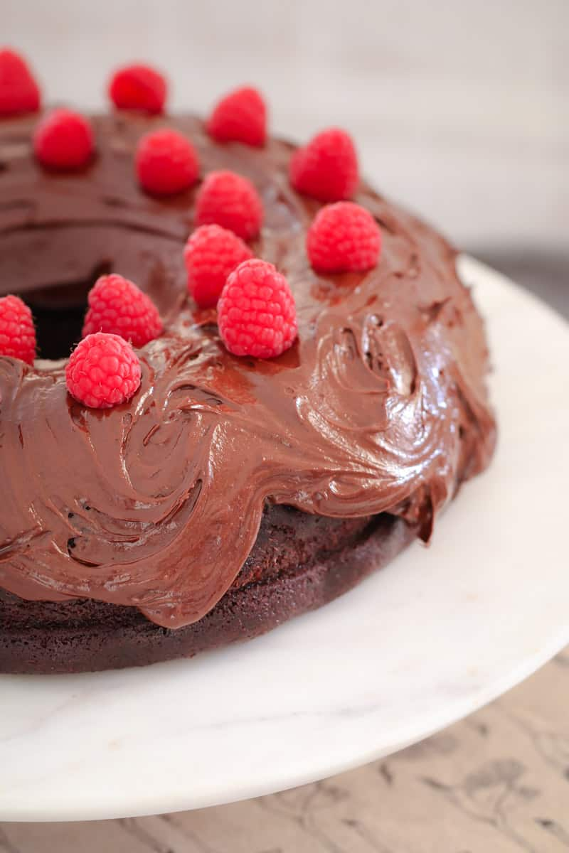 A close up of a chocolate mud cake decorated with chocolate frosting and fresh raspberries