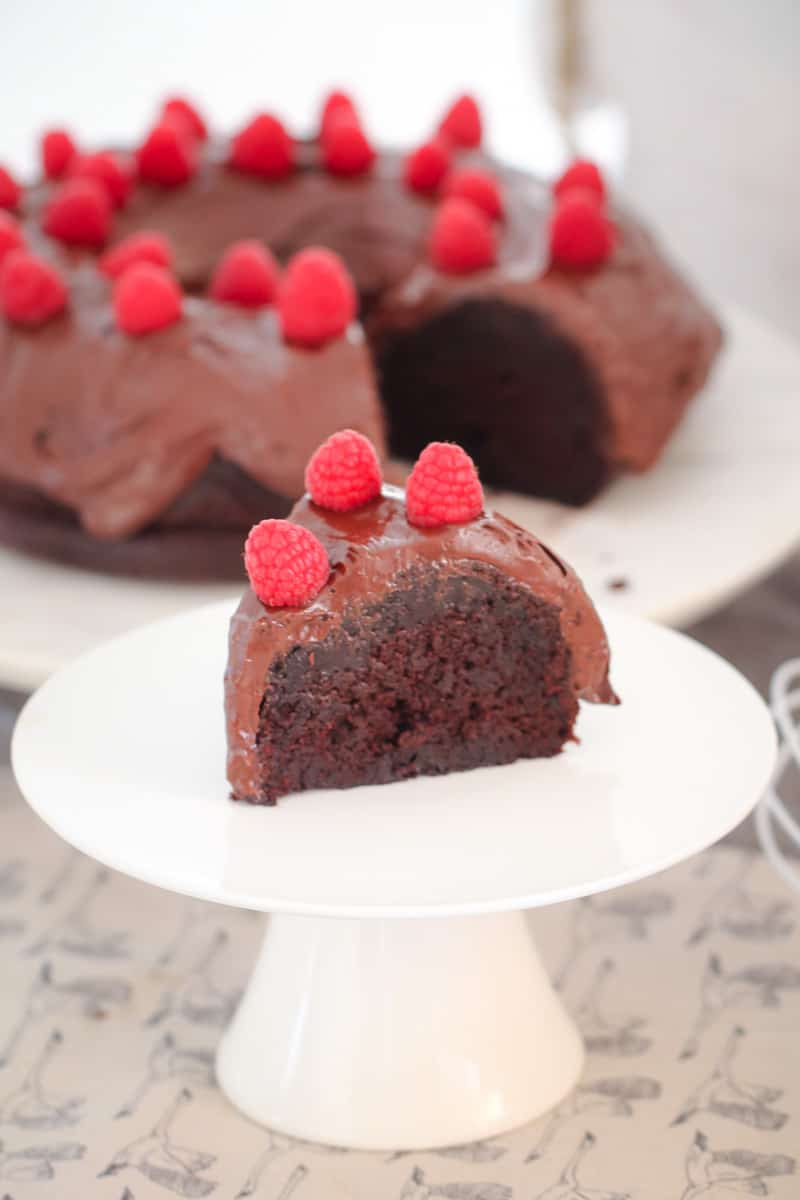 A slice of mud cake with chocolate ganache and raspberries, served on a plate with the rest of the cake in the background