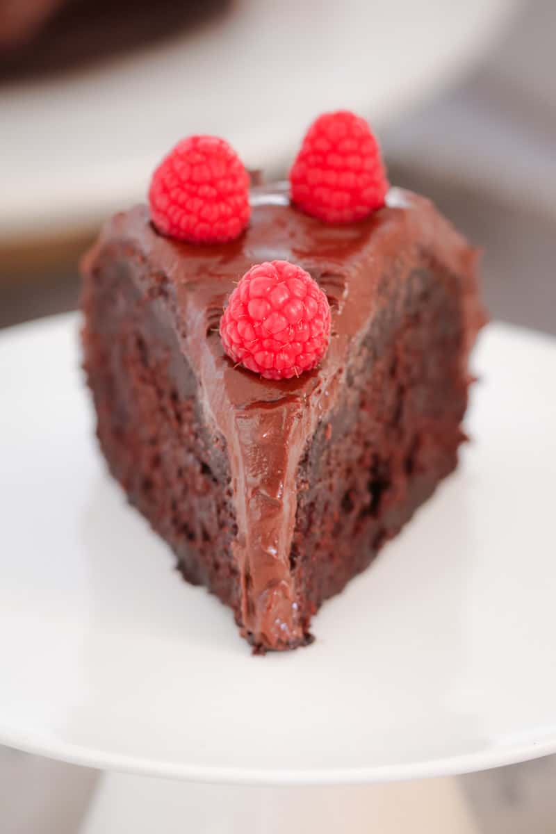 A close up of a slice of chocolate mud cake on a plate, with chocolate ganache and fresh raspberries