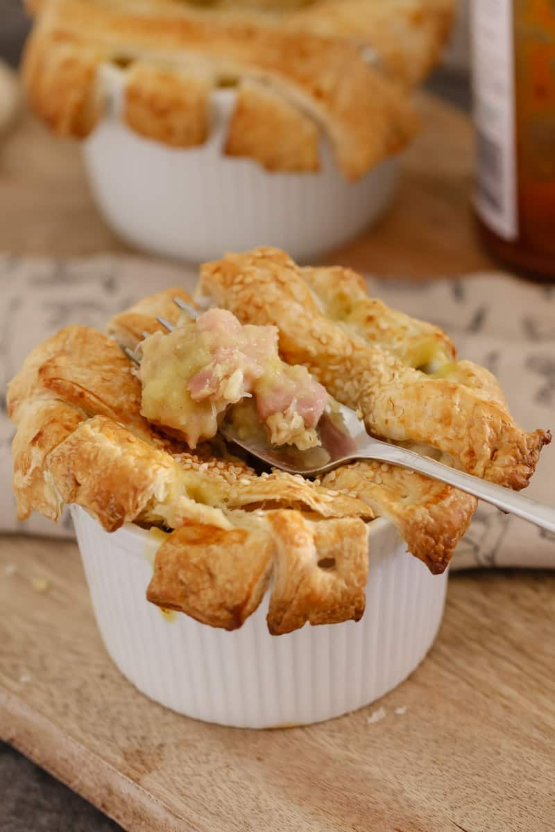 A forkful of a chicken and leek pie on top of the pastry lattice strips overlapping the sides of a small white ramekin