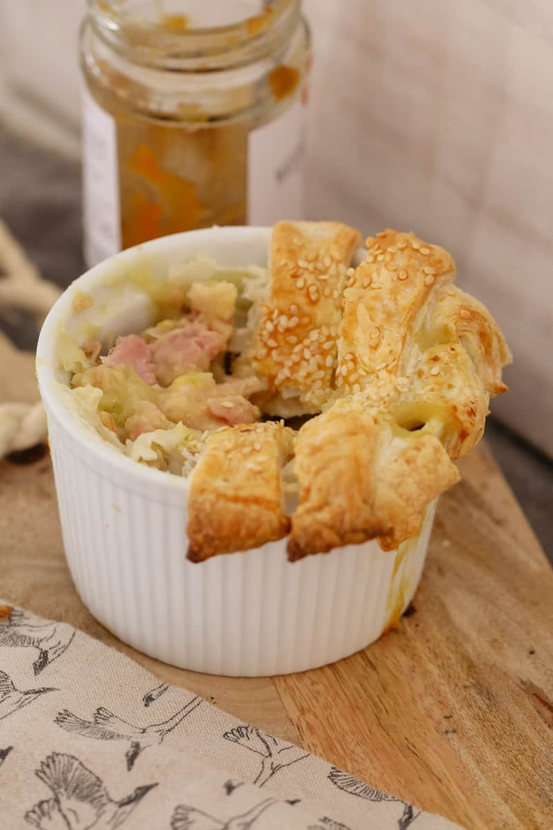 A chicken and leek pie in a small white ramekin with some of the pastry top removed to show filling