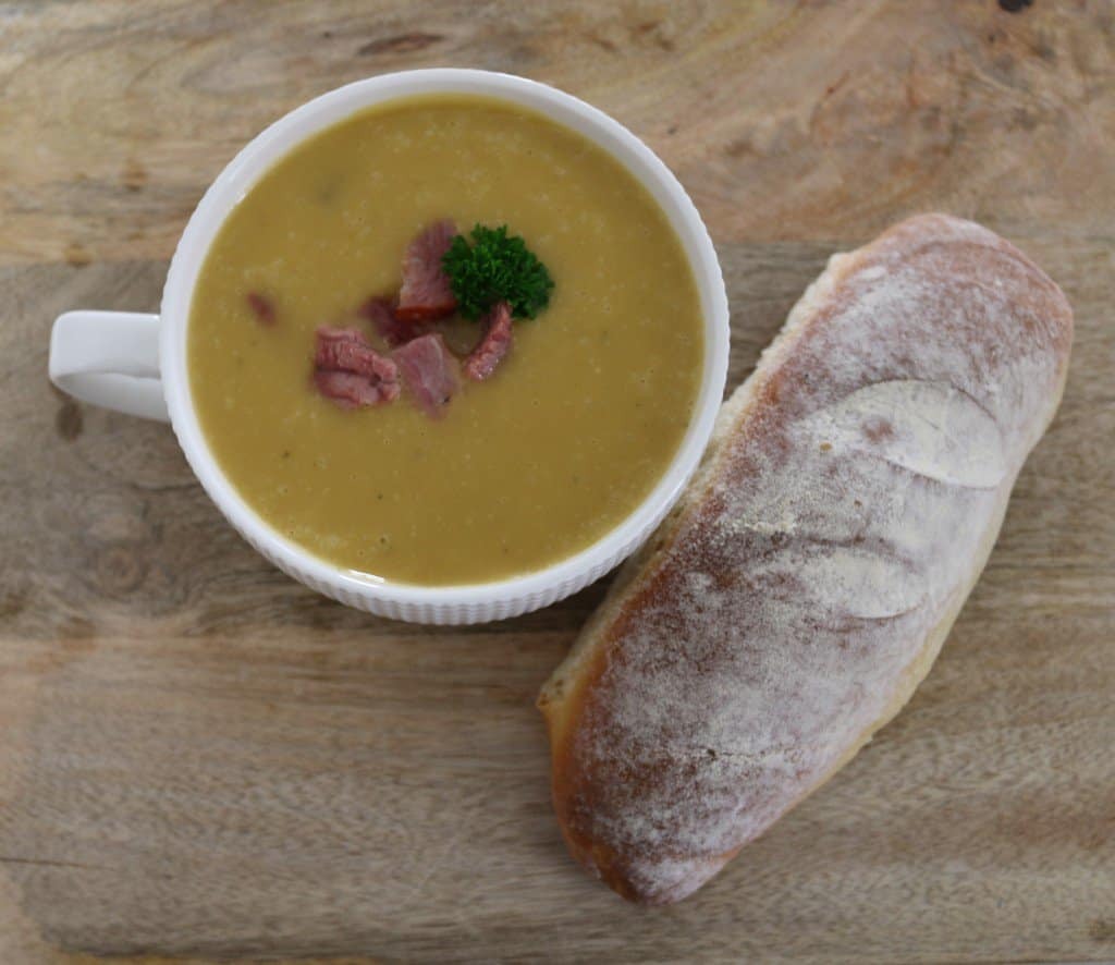 A cup of ham, potato and leek soup with extra ham on top and a bread roll on the side.