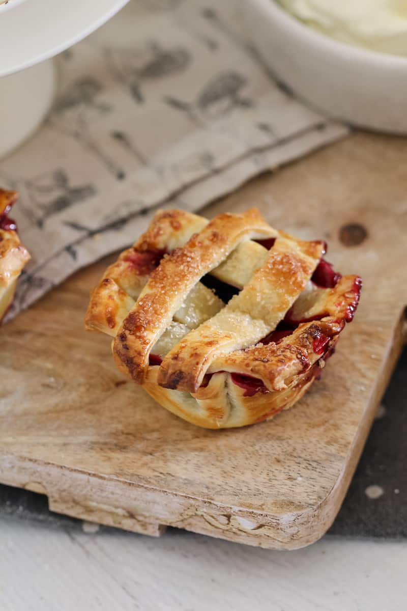 A mini pie filled with mixed berries and topped with a pastry lattice sitting on a wooden cutting board