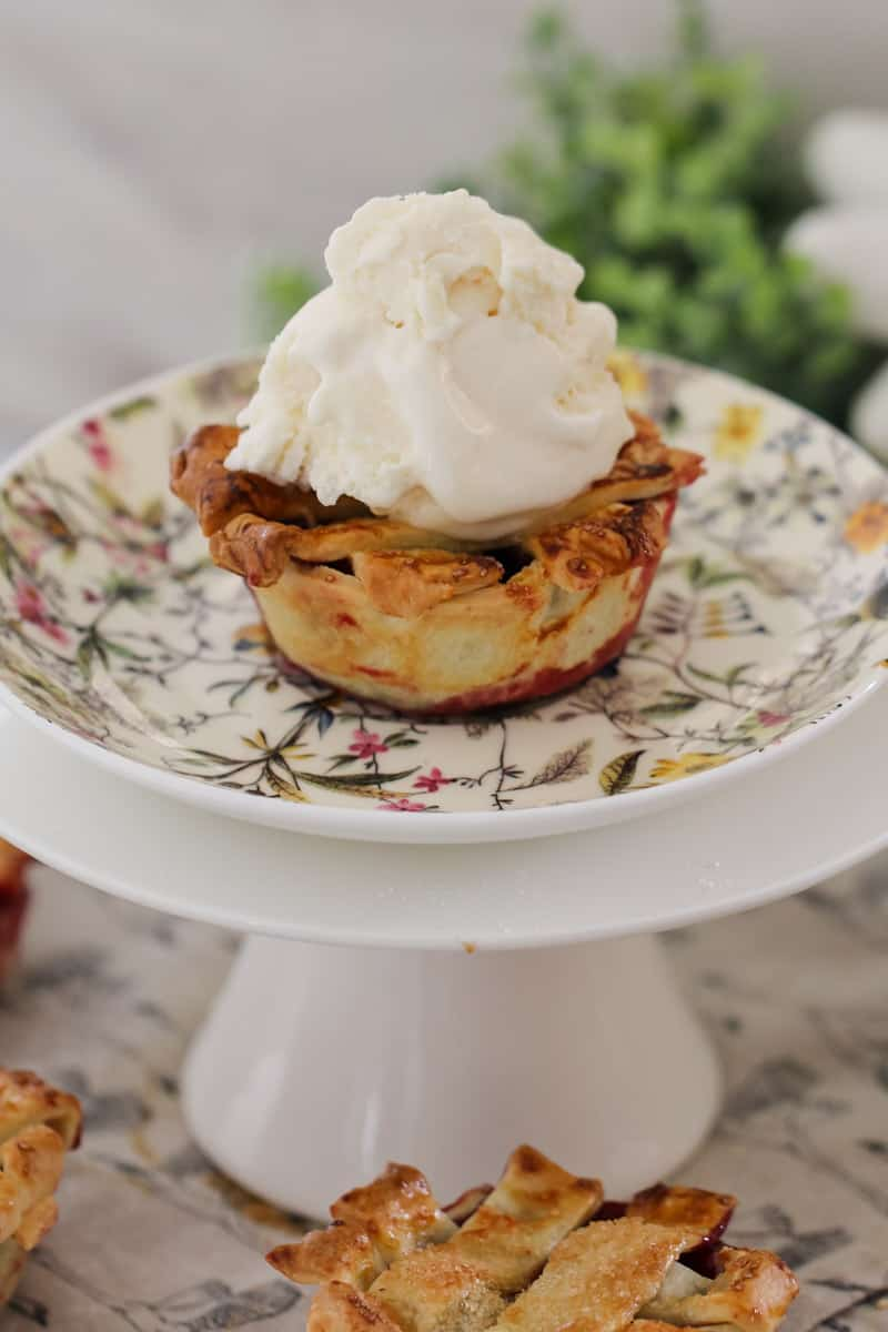 A mini pie filled with mixed berries and topped with a pastry lattice and whipped cream served on a floral plate