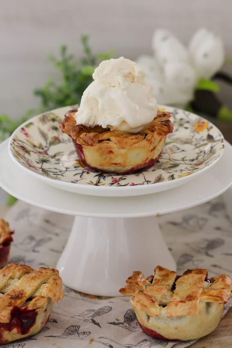A mini berry pie topped with a scoop of ice cream on a floral plate which sits on a white cake stand